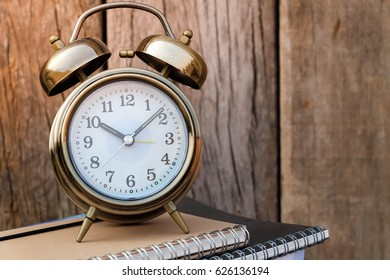 alarm clock and book with old wood background