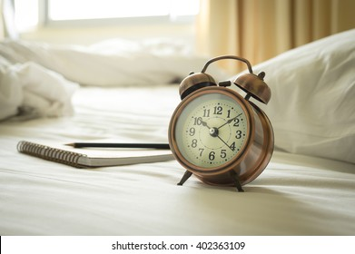 Alarm clock with book and pencil on bed.