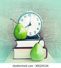 Alarm clock, book stack and felt pens. Schoolchild and student studies accessories. Back to school concept.
