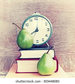 Alarm clock, book stack and pears. Schoolchild and student studies accessories. Back to school concept.