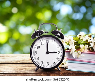 Alarm clock with books and spring blooming branch on wooden table against foliage background. Time change concept