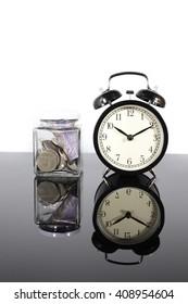 Alarm clock and bottle of money on white background