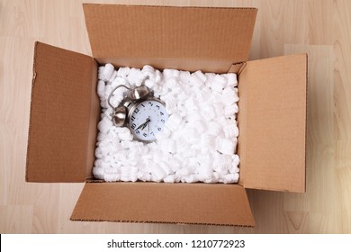 Alarm clock in a cardboard box full of packing peanuts