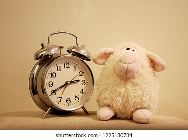 An alarm clock and a children's stuffed animal toy in soft, sleepy colors