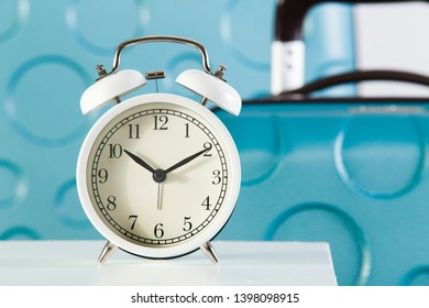 Alarm clock close-up at baggage background. Boarding time concept.