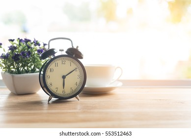 Alarm clock closeup have a good day with a cup of coffee and flower pots background in the morning sunlight.