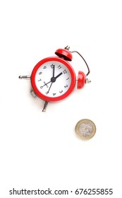 An alarm clock and  coins isolated on a white background