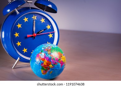 Alarm clock with the colors of the EU flag for an hour and small world ball. Symbolizing the time change in the EU, as well as the vote on its abolition.