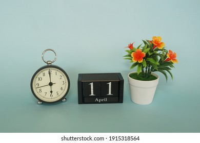 alarm clock with cube date and flower on the blue background. April 11 concept.