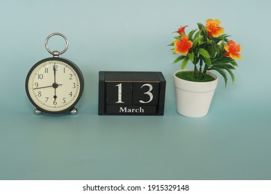 alarm clock with cube date and flower on the blue background. March 13 concept.