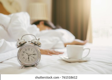 Alarm clock and cup of coffee standing on white bed has already rung early morning to wake up and woman is stretching on bed background. Relaxing concept.