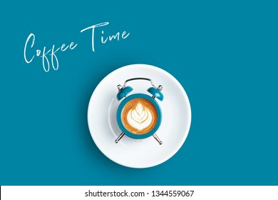 Alarm clock with the dial of cappuccino on blue background. Minimal styled coffee time concept with inscription Coffee Time.