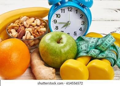 Alarm clock, dumbbells and apple. Eat and sleep rightl.