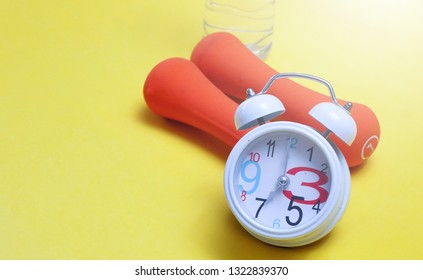 Alarm clock and dumbbells. Fitness concept
