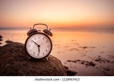 Alarm clock early in the morning on a rock by the sea in the sunrise
