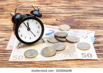 Alarm clock with euro bills and coins on the wooden table. Business concept.