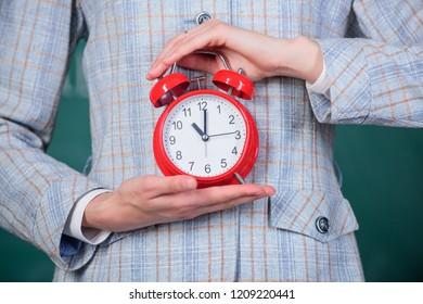 Alarm clock in female hands close up. Teachers attributes. Alarm clock in hands of teacher or educator classroom chalkboard background. School discipline concept. Schedule and regime.