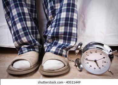 Alarm clock in the floor near an recently awake man