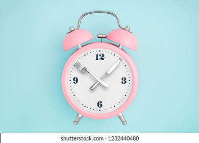 Alarm clock. Fork and knife instead of clock hands. Concept of intermittent fasting, lunchtime, diet and weight loss