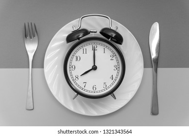 Alarm clock with fork and knife on the table. Time to eat, Breakfast, Lunch time and dinner concept. Black and White Concept