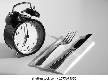 Alarm clock with fork and knife on the plate. Time to eat. Weight loss or diet concept. An image of a retro clock showing 7:00 am/pm.