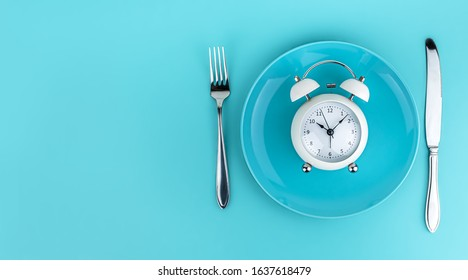 Alarm clock with fork and knife on the table. Time to eat, Breakfast, Lunch Time and Dinner concept