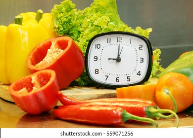 alarm clock with fresh vegetables for cooking,focus of alarm clock