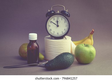 Alarm clock, fruits and toilet paper on a dark background. Natural remedy for constipation