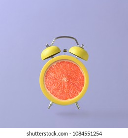 Alarm clock with grapefruit on colorful background. Summer time concept. Creative minimal still life.