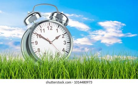 Alarm clock in green grass, 3d rendering