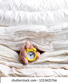 alarm clock in hand among blankets. Hand holding alarm clock among blankets, in bed. concept of laziness, sleep, world sleep day. time to get up.
