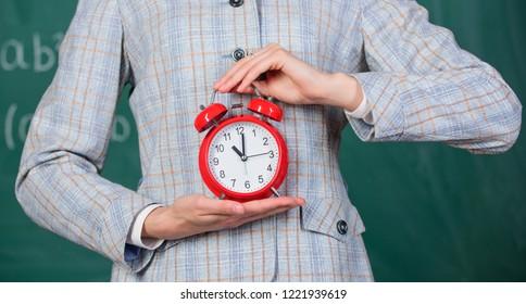 Alarm clock in hands of teacher or educator classroom chalkboard background. School discipline concept. Schedule and regime. Alarm clock in female hands close up. Teachers attributes.