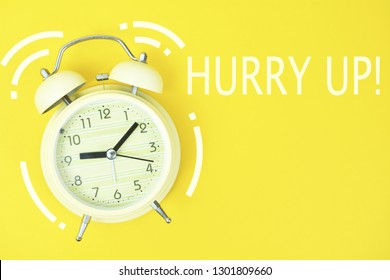 Alarm clock and hurry up text on yellow background.