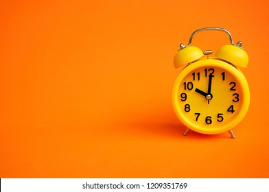 Alarm clock isolated on orange background with copy space