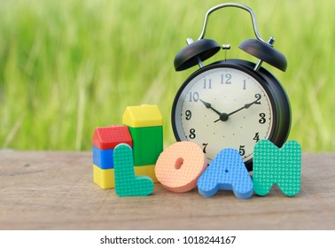 Alarm clock, kid toy block and alphabet on wood with blurry green bokeh in background. Concept of  banking loan.