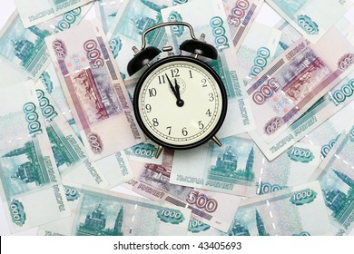 The alarm clock lays on the Russian banknotes.