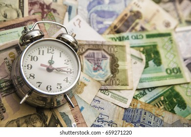 Alarm clock lie on dollars and money bill of different lands . Time is money concept , idea, symbol. empty copy space for inscription or objects.