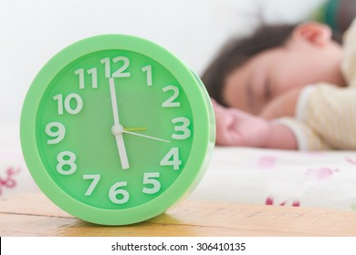 alarm clock with little boy sleeping on bed, green alarm clock, wooden table,