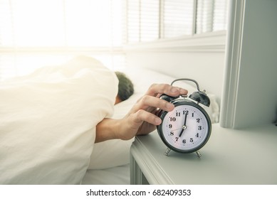 Alarm clock ,little man lazy to wake up to work on the bed