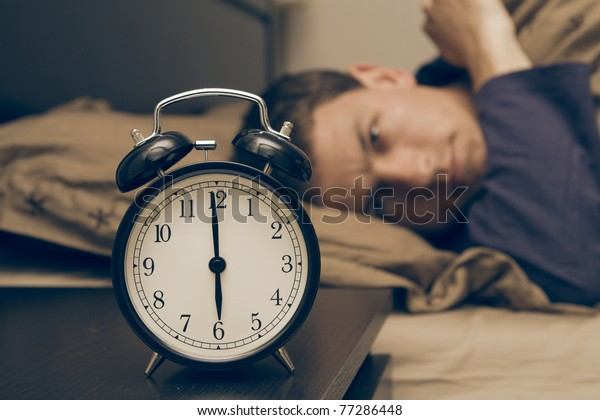 Alarm clock with male model in bed in background. Shallow depth of field.