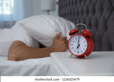 Alarm clock and man covering head with pillow in bedroom. Time of day