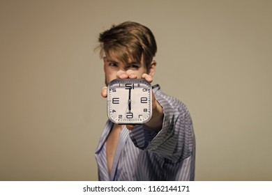 Alarm clock in man hand show six oclock on grey background. Time, routine, deadline. Morning, wake up concept, copy space