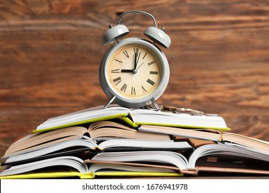 Alarm clock, money and books on table. Time management concept