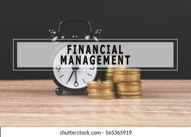 Alarm clock and money coin stack on wooden table and black background with text FINANCIAL MANAGEMENT. Finance concept, copy space.