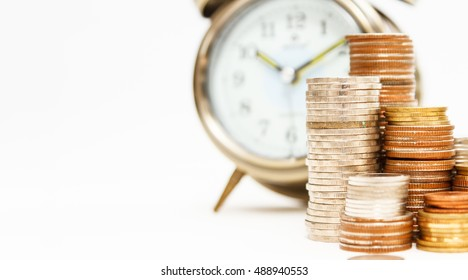 Alarm clock and money coins stack on white background,finance concept,business background and selective focus, copy space.