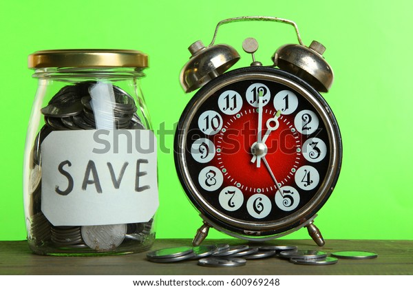 Alarm clock and money on a wooden table on a green background. Conception time is money