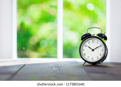 Alarm clock with morning sunlight and green bokeh nature background