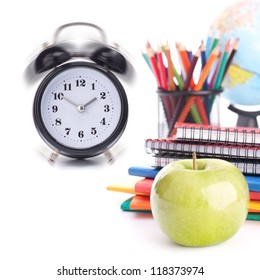 Alarm clock, notebook stack and pencils. Schoolchild and student studies accessories. Back to school concept.