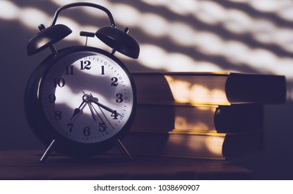 Alarm clock and old books on the shelf in the morning, concept of education and reading