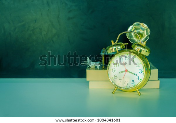 alarm clock old vintage gold and book - plane plastic. over white on black background. with copy space add text. color cinematic Vintage style tone. Concepts Education - Business